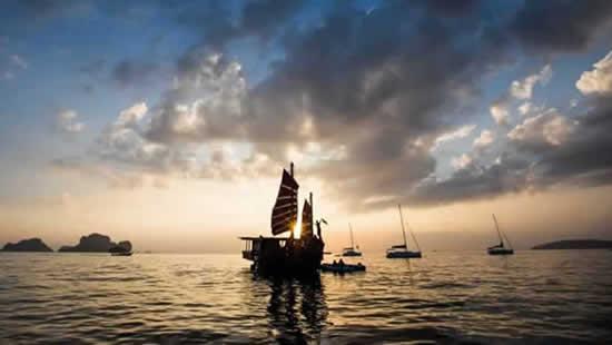 Voilier siamois naviguant au coucher de soleil aux alentours de Krabi